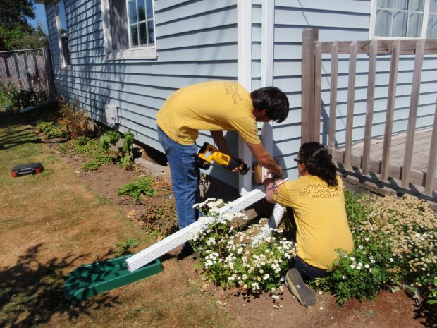 AmeriCorps volunteers disconnect downspouts