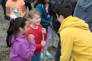 High school students help elementary students plant a native plant garden at their school.