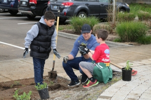 Older students help younger students plant a native plant garden at their school