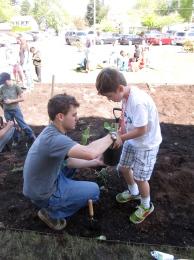 High school students help elementary students plant a rain garden at their school